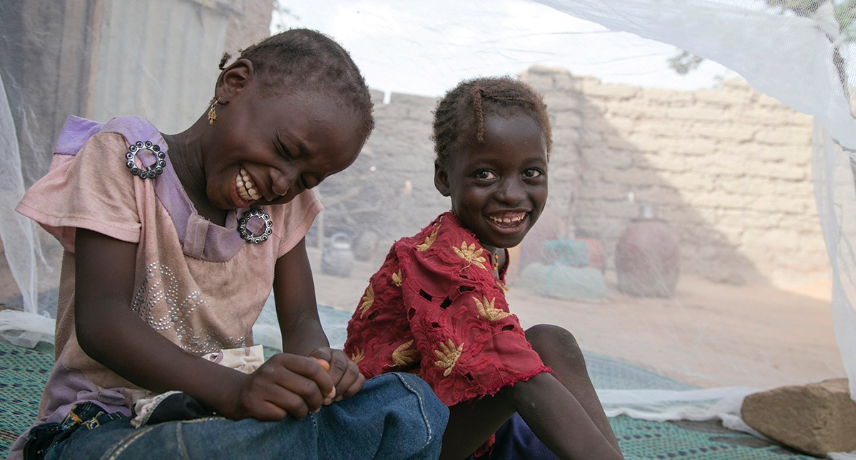 Mariama and her sister, Balkissa Abdou, sit under their mosquito net in Niger. The girls also received medicine to prevent malaria. Photo by Michael Stulman/CRS
