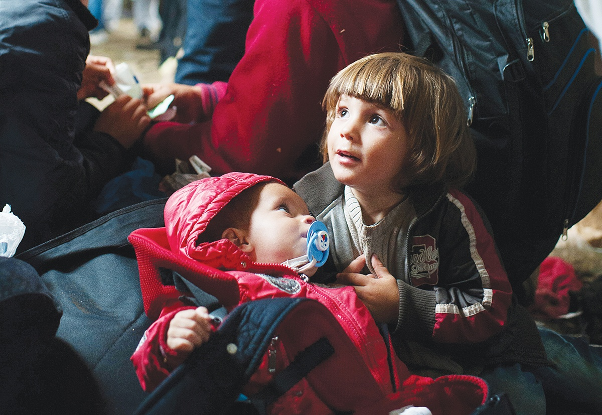Syrian cousins wait inside a tent at Vasariste, a refugee aid point in the Serbian border town of Kanjiza. Photo by Kira Horvath for CRS